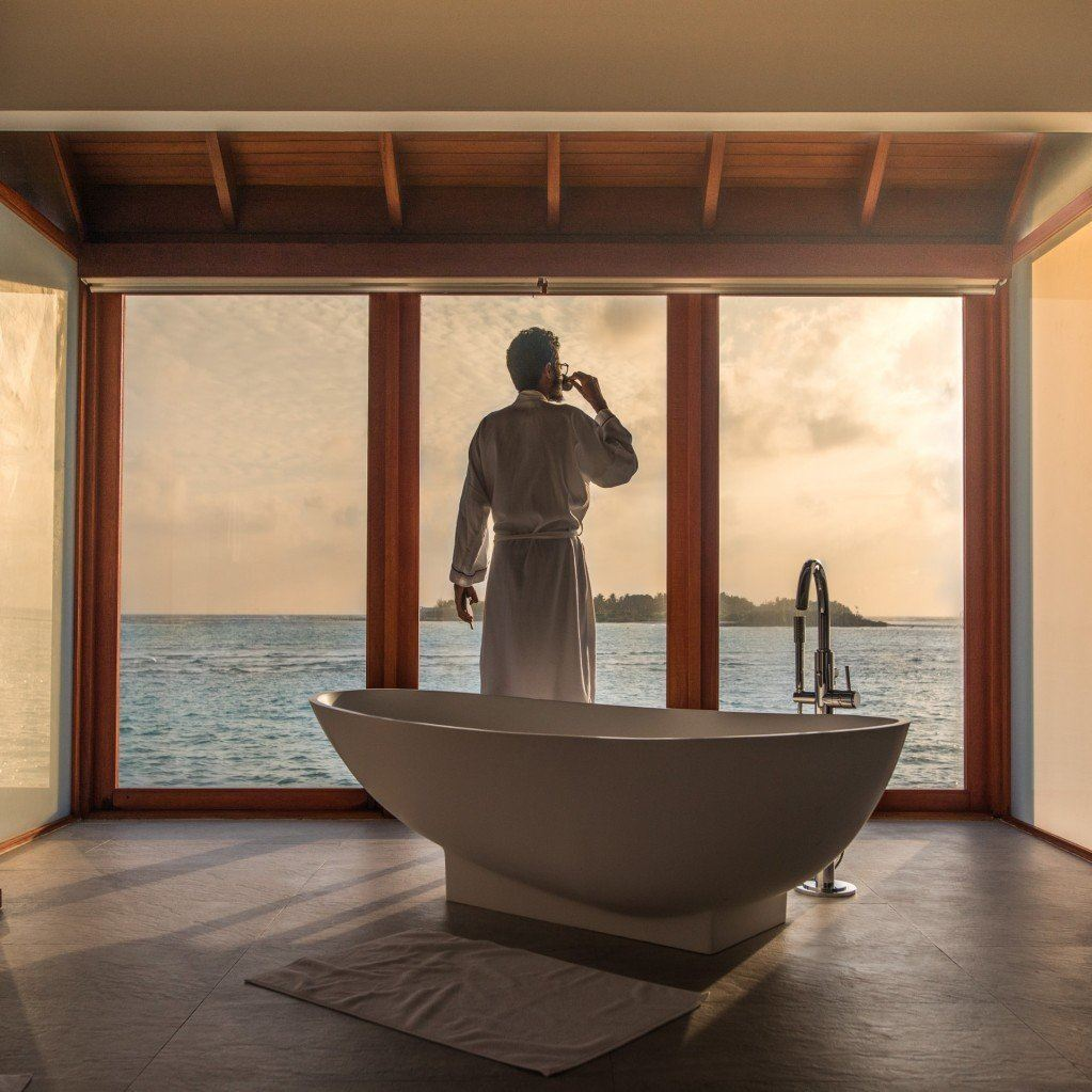 man in bathrobe in expensive suite looks out over sea