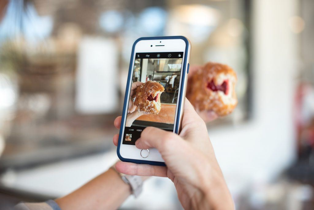 influencer taking a picture of a donut