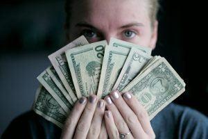 person holding a fan of dollar bills